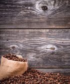 Sack of coffee grains against wooden background — Stock Photo