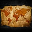 Antique world map in black wooden background — Stock Photo #35286541