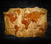 Antique world map in black wooden background — Stock Photo