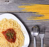 Spaghetti bolognese with tomato beef sauce and raw pasta on woo — Stock Photo