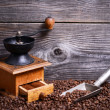 Manual coffee grinder with beans and vintage scoop on wooden bac — Stock Photo
