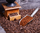 Antique coffee grinder with grinded coffee in scoop on beans — Stock Photo