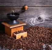 Manual coffee grinder with beans on wooden background — Stockfoto