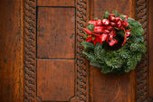 Christmas wreath on wooden door decoration — Stock Photo