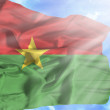 Burkina Faso waving flag against blue sky with sunrays — Stock Photo