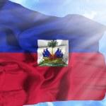 Haiti waving flag against blue sky with sunrays — Stock Photo