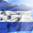 Honduras waving flag against blue sky with sunrays — Stock Photo
