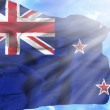 New Zealand waving flag against blue sky with sunrays — Stock Photo