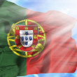 Portugal waving flag against blue sky with sunrays — Stock Photo