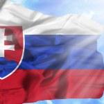 Slovakia waving flag against blue sky with sunrays — Stock Photo
