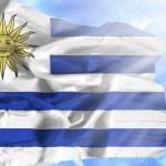 Uruguay waving flag against blue sky with sunrays — Stock Photo