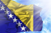Bosnia and Herzegovina waving flag against blue sky with sunrays — Stock Photo