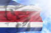 Costa Rica waving flag against blue sky with sunrays — Stock Photo
