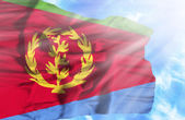 Eritrea waving flag against blue sky with sunrays — Stock Photo