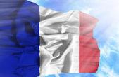 France waving flag against blue sky with sunrays — Stock Photo