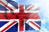 Great Britain waving flag against blue sky with sunrays — Stock Photo