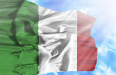 Italy waving flag against blue sky with sunrays — Stockfoto