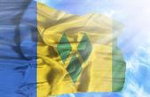 Saint Vincent and Grenadines waving flag against blue sky with s — Foto de Stock