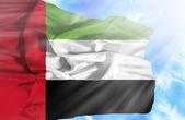 United Arab Emirates waving flag against blue sky with sunrays — Stock Photo