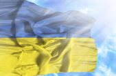 Ukraine waving flag against blue sky with sunrays — Stock fotografie
