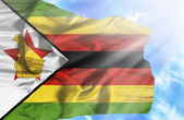 Zimbabwe waving flag against blue sky with sunrays — Stock Photo