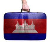 Tourist hand holding vintage leather travel bag with flag of Cam — Stock Photo