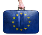 Tourist hand holding vintage leather travel bag with flag of Eur — Stock Photo