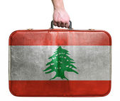 Tourist hand holding vintage leather travel bag with flag of Leb — Stock Photo