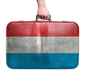 Tourist hand holding vintage leather travel bag with flag of Lux — Stock Photo