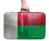 Tourist hand holding vintage leather travel bag with flag of Mad — Stock Photo