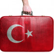 Tourist hand holding vintage leather travel bag with flag of Tur — Stock Photo #39397615