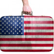 Tourist hand holding vintage leather travel bag with flag of Uni — Stock Photo #39398059