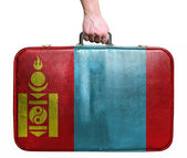 Tourist hand holding vintage leather travel bag with flag of Mon — Stock Photo