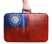 Tourist hand holding vintage leather travel bag with flag of Mya — Stock Photo