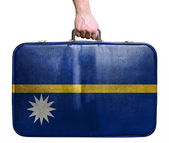 Tourist hand holding vintage leather travel bag with flag of Nau — Stock Photo