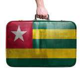 Tourist hand holding vintage leather travel bag with flag of Tog — Stock Photo