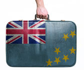 Tourist hand holding vintage leather travel bag with flag of Tuv — Stock Photo