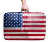 Tourist hand holding vintage leather travel bag with flag of Uni — Stock Photo