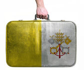 Tourist hand holding vintage leather travel bag with flag of Vat — Stock Photo