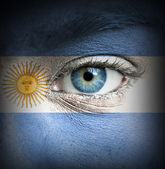 Human face painted with flag of Argentina — Stock Photo