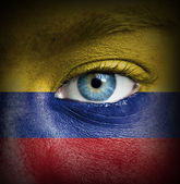 Human face painted with flag of Colombia — Stock Photo