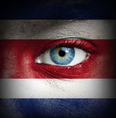 Human face painted with flag of Costa Rica — Stock Photo
