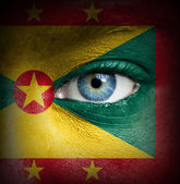 Human face painted with flag of Grenada — Stock Photo