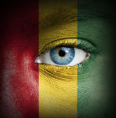Human face painted with flag of Guinea — Stock Photo