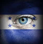 Human face painted with flag of Honduras — Stock Photo