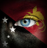Human face painted with flag of Papua New Guinea — Stock Photo