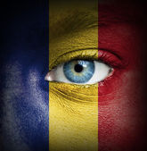 Human face painted with flag of Romania — Stock Photo