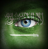 Human face painted with flag of Saudi Arabia — Stock Photo