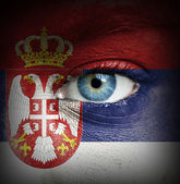 Human face painted with flag of Serbia — Stock Photo