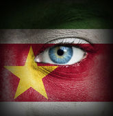 Ludzka twarz malowane z flaga surinamu — Zdjęcie stockowe